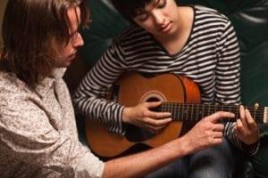 bigstock-Young-Musician-Teaches-Female--9351650